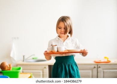 child girl in a linen apron with a tray lays the table, developing sensory activities in montessori and earlier child development, independence of children and helping mother