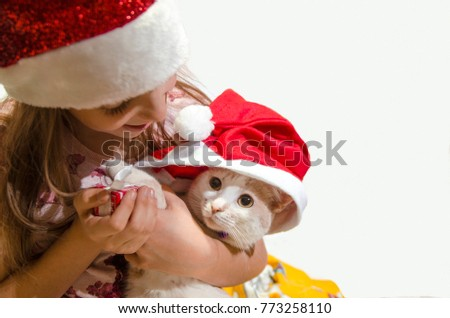 7daefc5c1f567 Child Girl with little white cat hold her in arms. Cute cat face with Santa