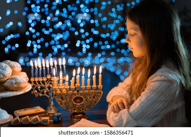 Child girl Looking at Menorah Candles on wooden table and sufganiyot on background light glitter bokeh overlay. Hanukkah jewish holiday Israel hebrew traditional family celebration invitation design