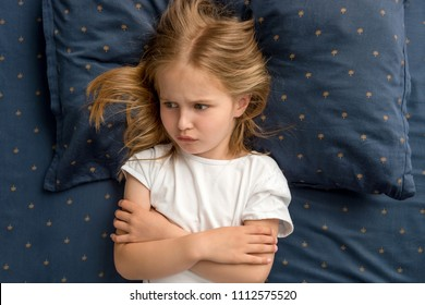 Child girl lying on the bed refuses to sleep