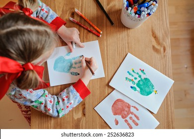 child girl making christmas hand prints post cards at home