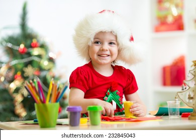 child girl making christmas tree of plasticine