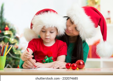 child girl and mom writing christmas letter to Santa Claus