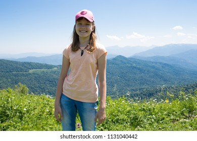 Child Girl In Mountains On Green Grass Under Blue Sky