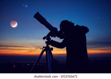 Child girl observing stars, planets, Moon and night sky with astronomical telescope.