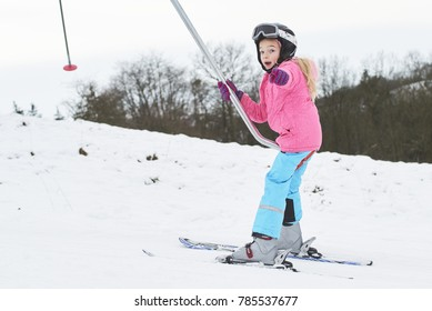 Child girl on a button ski lift going uphill in the mountains. Kids in winter sport school in ski resort. Family fun in the snow. Little skier learning and exercising on a slope.