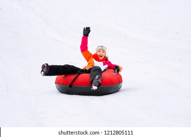 Child girl on snow tubes downhill at winter day.