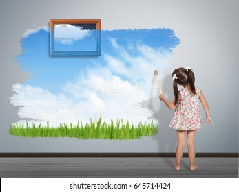 child girl with paint brush painting wall, back view