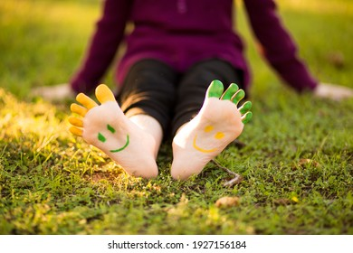 Child girl with painted foot on green grass having fun outdoors in spring park.