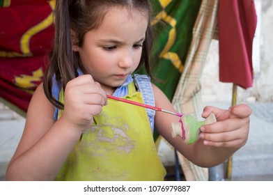 Child girl painting little clay piece with purple. Ceramic workshop for children concept