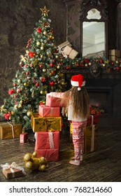 child girl in pajamas and Christmas hat playing with gifts in living room in the evening