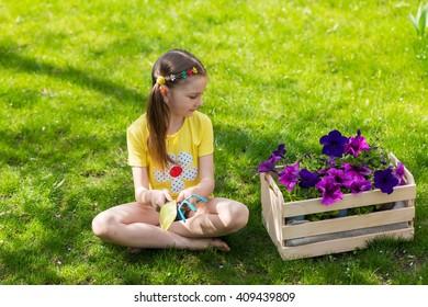 child girl planting flowers in spring garden