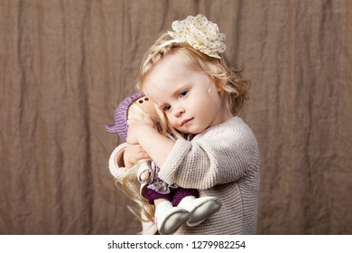 Child girl playing with a dall. Little cute girl with natural toys.