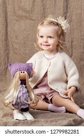 Child girl playing with a dall. Little cute girl with natural toys.  Copy space
