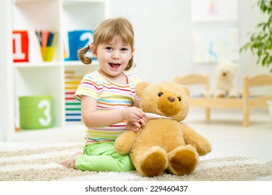 child girl playing doctor with plush toy at nursery