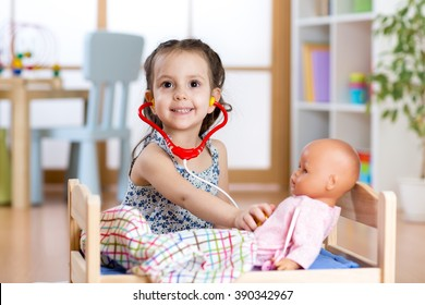 child girl playing doctor role game examining her doll using stethoscope sitting in playroom at home, school or kindergarten