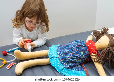 Child girl playing doctor with a toy. Profession and care concept. Clear neutral background.