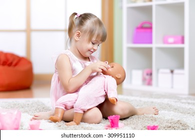 child girl playing with her baby-doll in day care center