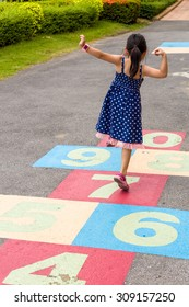 Child Girl Playing Hopscotch on Playground