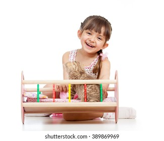 Child girl playing with a kitten and rocking him in doll crib