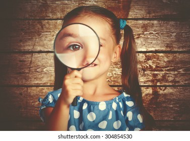 child girl playing with a magnifying glass in the detective