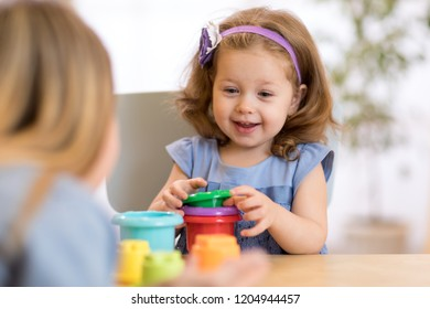 Child girl playing stacking cups at home