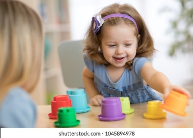 Child girl playing at table in kindergarten