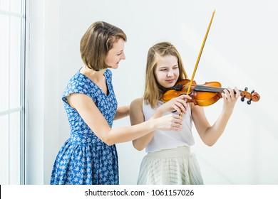 Child girl playing the violin is engaged with the teacher beautiful and happy in the white room with a window