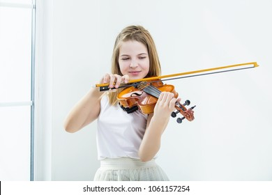 Child girl playing the violin to study beautiful and happy in a white room with window