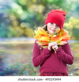 Child girl portrait outdoors autumn nature background empty space.Female kid portrait with yellow leaves bouquet walking in park.