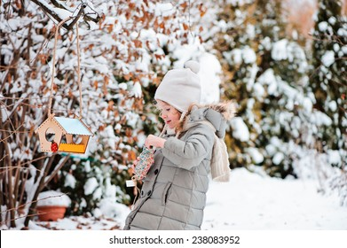 Child girl pour seeds in bird feeder in winter snowy garden