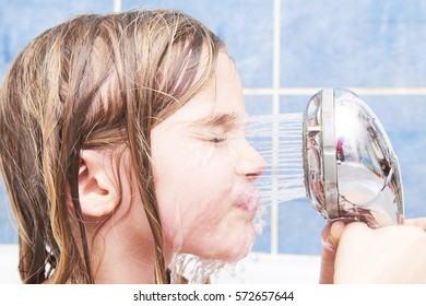Child girl pours water from the shower at her face in bathtub