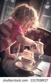 Child girl preparing traditional classic English breakfast tea