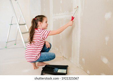 Child girl priming and painting walls with a roller during house renovation. Home repairs with family. Update, improvement living room with kids.