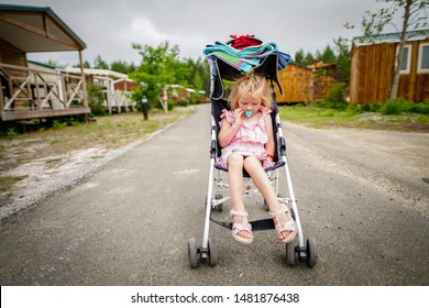 Child girl in a pushchair. Cute child girl in stroller.