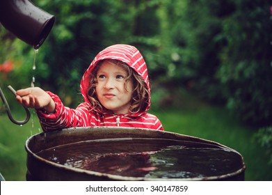 child girl in raincoat playing with barrel of water in summer garden, rainy day activities
