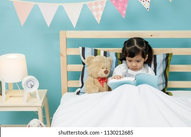 Child girl reading a book with her teddy bear on the wooden bed in her bedroom, learning concept at home