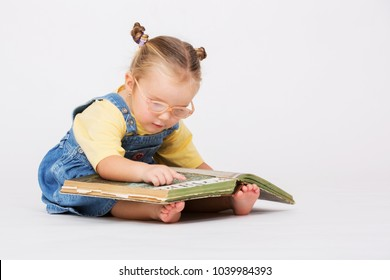 Child girl reading book. Pretty girl sitting with book and reading over white.