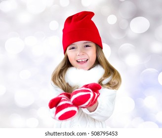 Child girl in red hat and gloves stretching empty hands christmas advertisement concept.Holiday background idea.Kid xmas clothing holding empty hand.