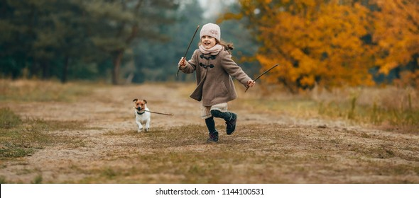 Child girl runs, has fun and plays with her dog during walk in autumn forest.