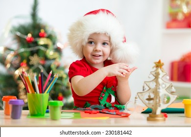 child girl in Santa hat making christmas tree of plasticine