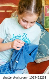 Child girl sews with a needle. Manual work.
