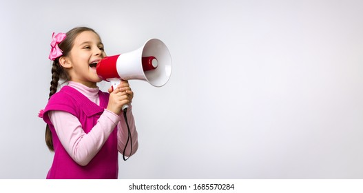 Child Girl Shouting Through Megaphone on Grey Background. Communication and Advertising Concept.