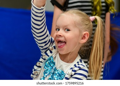 Child girl shows tongue at a party.