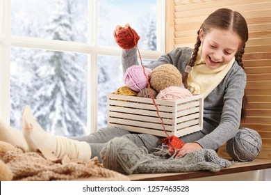 Child girl is sitting on a window sill with wool yarns and knitting. Beautiful view outside the window - sunny day in winter and snow.