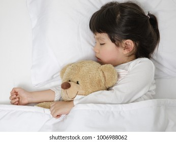 Child girl sleeping with teddy bear on the wooden bed in her bedroom, New family and baby healthy concept