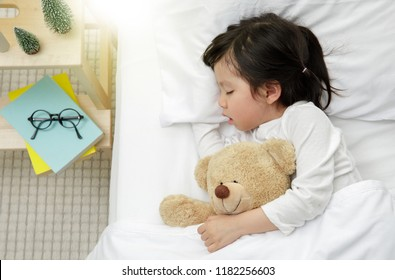 Child girl sleeping with teddy bear on the wooden bed in her bedroom, family concept at home