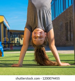 Child girl stands on hands upside down. Teen girl plays on the playground. Kid laughs, she has fun. Outdoor games concept. Happy child upside down