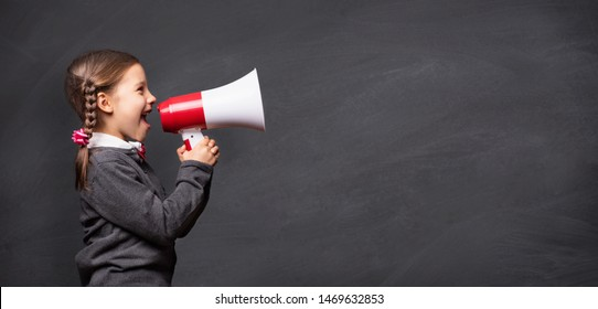 Child Girl Student Shouting Through Megaphone on Blackboard Backdrop with Available Copy Space. Back to School Concept.