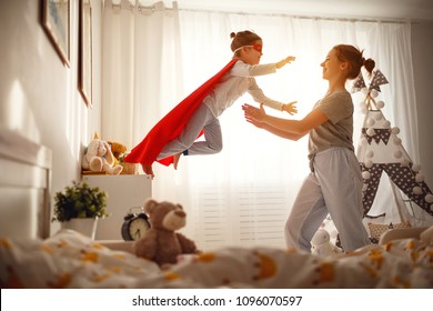 child girl in a super hero costume with mask and red cloak  at home